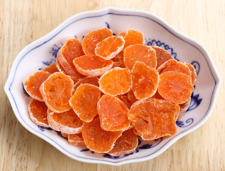 candied: Dried, candied fruits kumquats in porcelain bowl. Stock Photo
