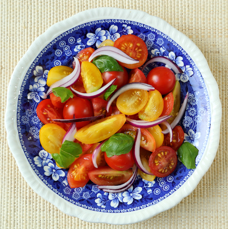 tomate ensalada: Colorful salad with red and yellow tomatoes with red onion and basil. Foto de archivo