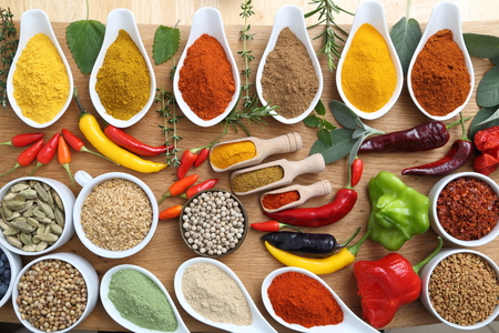 enebro: Aromatic and colorful spices in ceramic containers on a wooden background. Foto de archivo