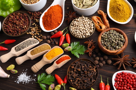 food additives: Herbs and spices on dark wooden background. Aromatic ingredients and natural food additives.