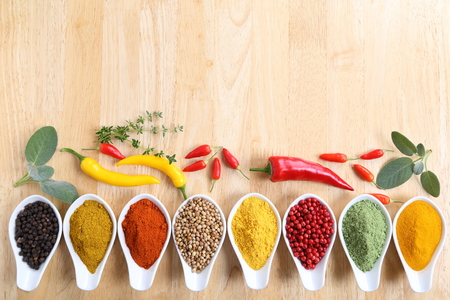 food additives: Aromatic and colorful spices in ceramic containers on a wooden background. Stock Photo