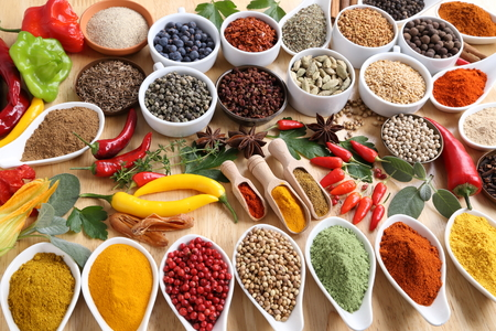 Aromatic and colorful spices in ceramic containers on a wooden background. Spice in the kitchen. Stock Photo