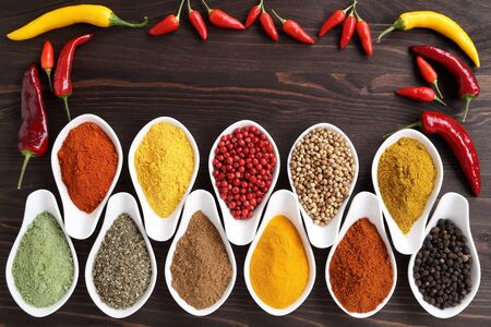Aromatic and colorful spices in ceramic containers on a wooden background. Stock Photo