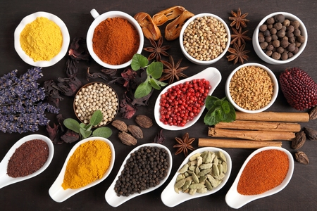 Colorful and aromatic herbs and spices on a dark wooden background. Stock Photo