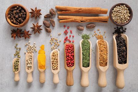 Spices on wooden spoon. Aromatic ingredients and natural food additives. Stock Photo