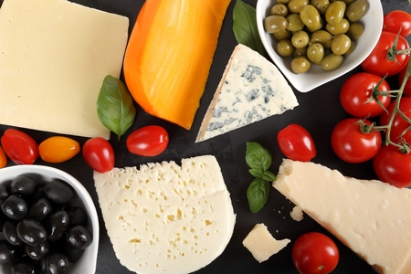 Food composition - different types of cheeses, olives and tomatoes.