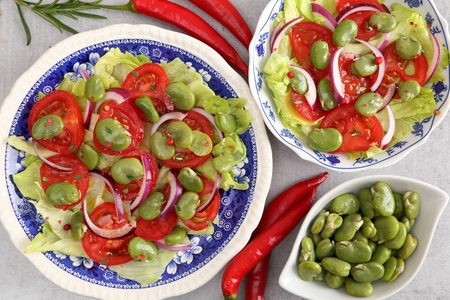 Close up of a broad beans salad with tomato and red onion. Stock Photo