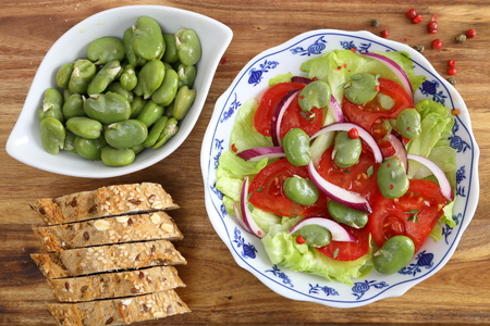 Salad with broad beans, tomatoes and red onion.