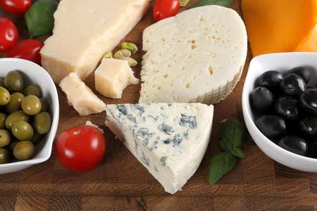 Delicacy. Food composition - different types of cheeses, olives and tomatoes. Stock Photo