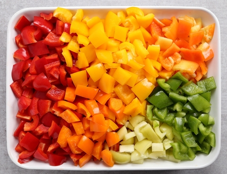 Colorful, chopped peppers in a ceramic dish.