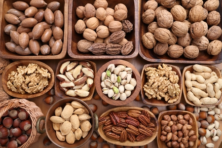 A variety of nuts in wooden bowls. Stock Photo