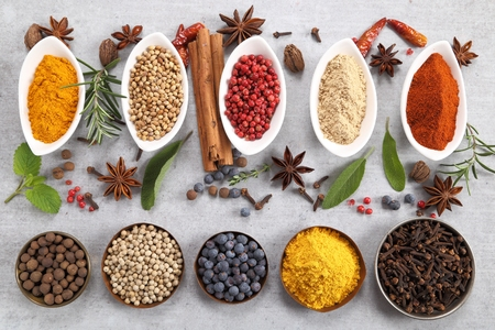 Spices and herbs in ceramic dishes on a gray background. Stock Photo