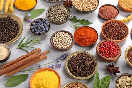 Colorful and aromatic herbs and spices on a gray ceramic background. Top view. Stock Photo