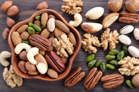 Different kinds of nuts in wooden bowl. Healthy food. 版權商用圖片