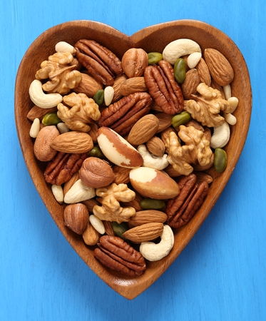 Different types of nuts in wooden bowl on a blue background. Top view.