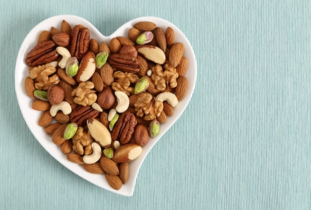 Different types of nuts on a plate in the shape of a heart. Top view.