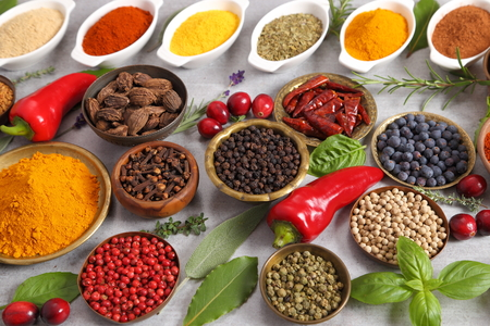 Colorful, aromatic spices and fresh herbs on a light background. Top view. Stock Photo