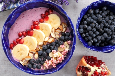 Healthy blueberry smoothie bowl with bannan, grenade, almonds, millet gruel. Imagens