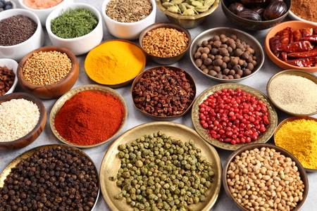 Aromatic spices and herbs in metal and ceramic bowls.