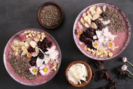 Smoothie bowl with blueberries, nuts, chia seeds and flowers for healthy vegan vegetarian diet breakfast.