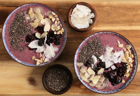 Smoothie bowl with blueberries, nuts, chia seeds and coconut flakes.