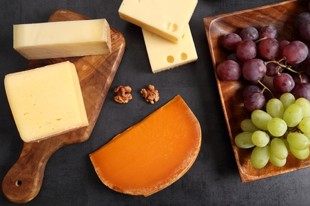 Different types of cheese on a wooden board and other snacks like nuts, olives, fruits.