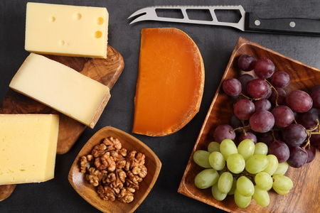 Different types of cheese on a wooden board and other snacks like nuts, fruits. Imagens