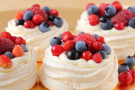 Dessert with berries on a meringue with cream. Archivio Fotografico