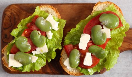 Sandwiches with broad beans, tomatoes and goat cheese. Stock fotó
