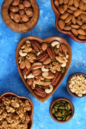 Different types of nuts in wooden bowls on a blue background. Top view.