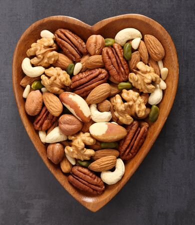 Different types of nuts in wooden bowl on a black background. Top view.