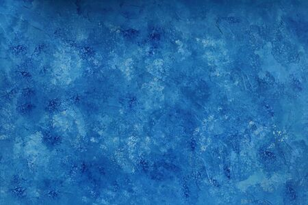 An abstract, painted blue background with an uneven surface