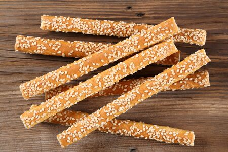 Bread sticks with salt and sesame seeds top view on a wooden  background. 免版税图像
