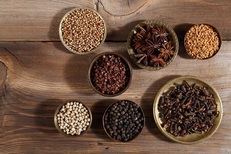Brown aromatic spices in metal bowls on a wooden background. Top view.