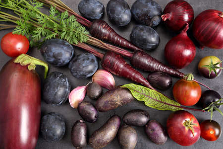Raw purple vegetables and fruits over black background. Flat lay. Top view. Stock Photo