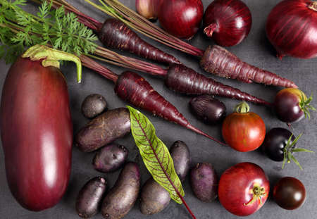 Raw purple vegetables over black background. Flat lay. Top view. Stock Photo