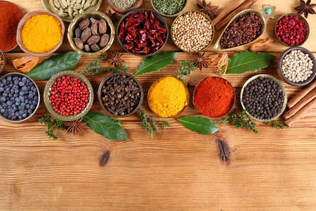 Spices in metal bowls on wooden background. Food and cuisine ingredients. Colorful natural additives. Stock Photo