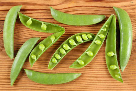 Sweet green peas on a wooden background. Top view. Stock Photo