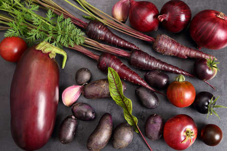 Raw purple vegetables over black background. Top view. Stock Photo