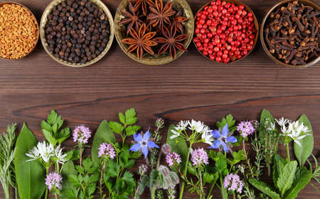 Herbs and spices on wooden background. Food and cuisine ingredients. Top view.