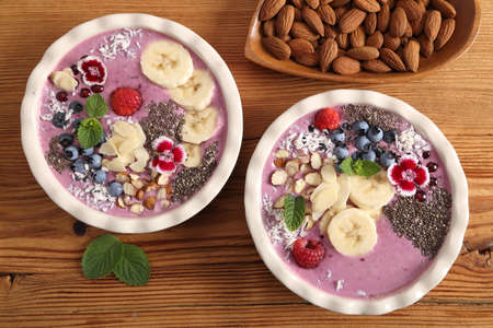 Smoothie bowl with blueberries, currants, chia seeds, banana and almonds on wooden background. Top view.