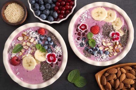 Smoothie bowl with blueberries, currants, chia seeds, banana and almonds. Top view.