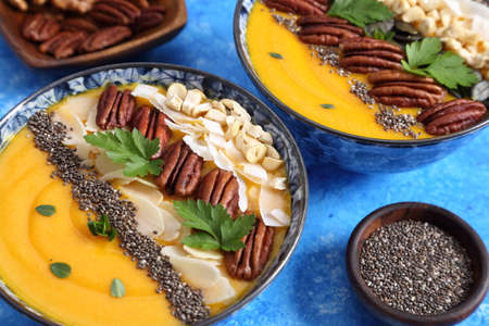 Smoothie bowl with pumpkin, pecan nuts, chia seeds and coconut flakes.