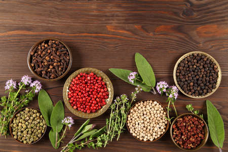 Colorful and aromatic herbs and peppers on a dark wooden background. Top view.