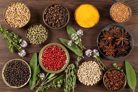 Colorful and aromatic herbs and spices on a dark wooden background. Top view.