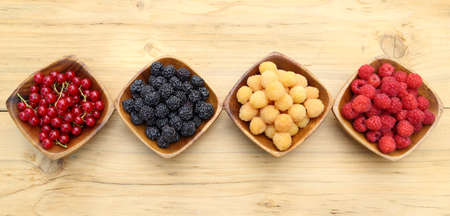 Red, black, white raspberries and currants in wooden bowls. Top view. Stock Photo
