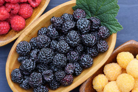 Red, black and white raspberries in wooden bowls. Top view.