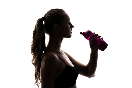 quench: Blonde girl is in anticipation of the fact that she would drink water from a pink sport bottle. She wants to quench your thirst Stock Photo