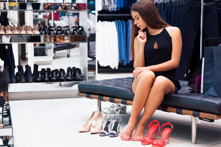 suited up: A girl picks up the shoes themselves. She thinks what would be better suited to her clothes Stock Photo