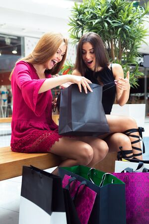 shoppingbag: The girls enjoy the acquired shopping in the store. They are shocked, because they found this clothes very fast.